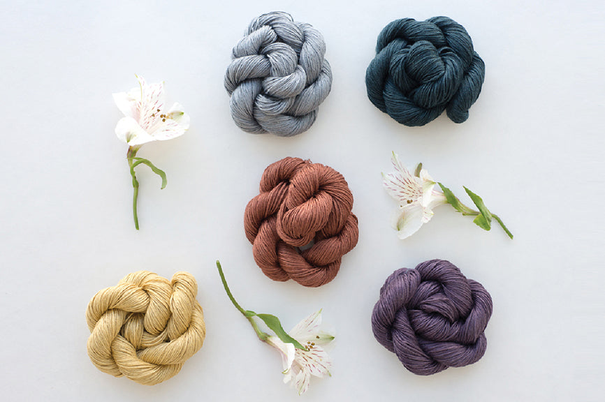 Five skeins of richly colored linen yarn sit in neatly twisted piles on a white background, with white flowers in between