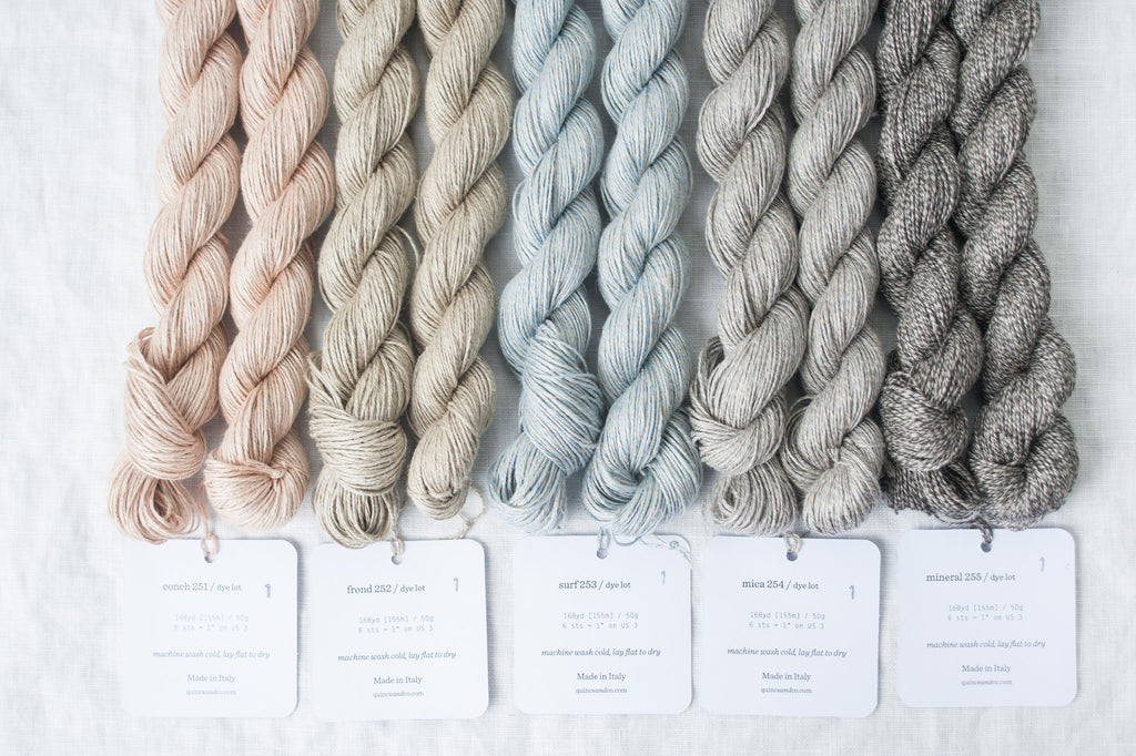 Skeins of marled linen yarn laid flat on a white linen backdrop, with their paper tags spread below them