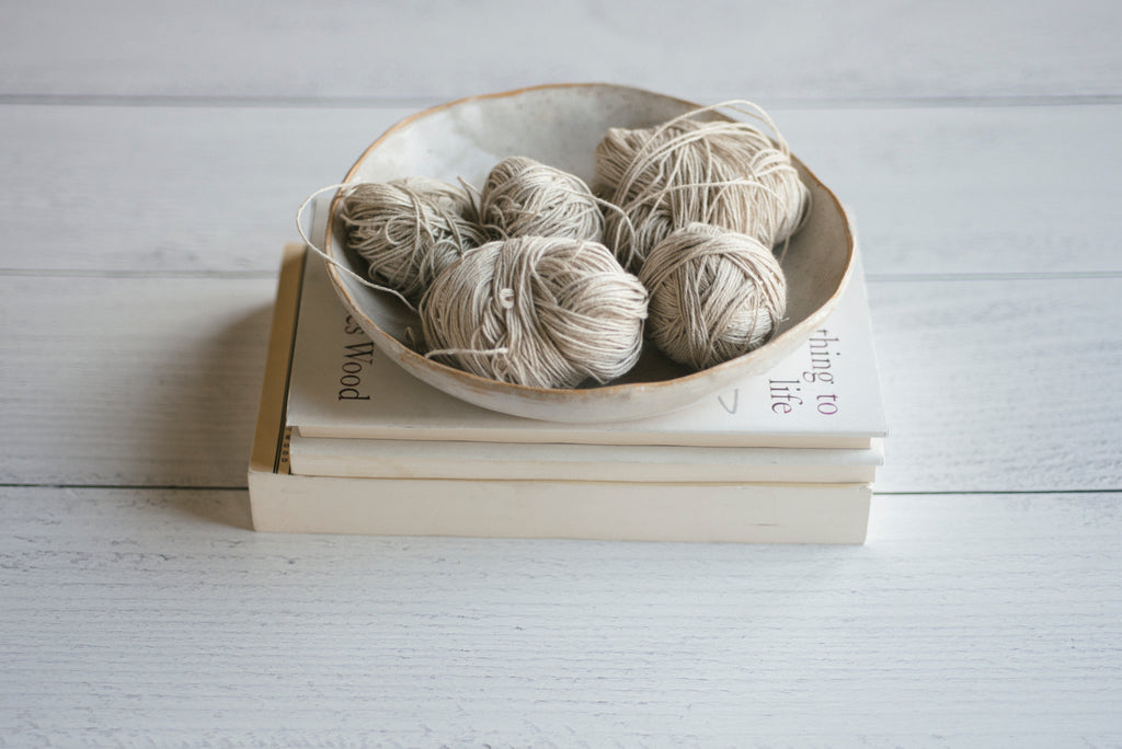 Hand-wound balls of natural linen yarn in a ceramic bowl, sitting on a stack of books