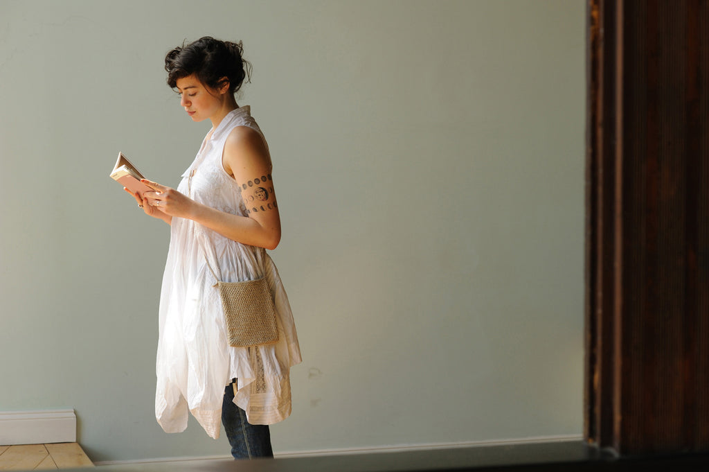 A woman in a white dress and blue jeans stands reading a book, wearing a small purse knitted in undyed linen