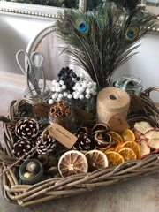 A basket containing wreath materials including, dried fruits, cinnamon and pine.