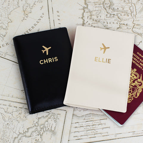 pair of matching leather passport covers personalised with names