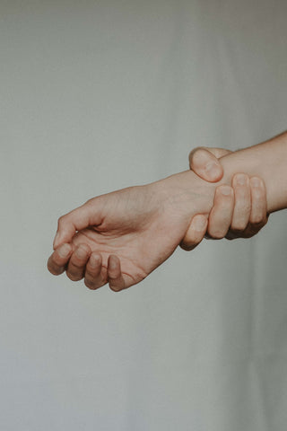A man grabbing his own wrist due to severe pain.