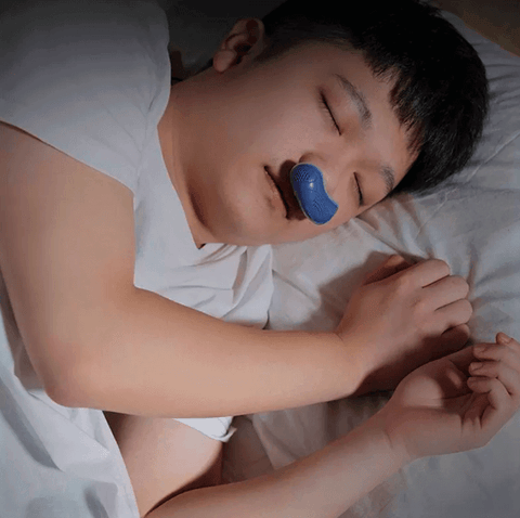 a sleeping young man wearing the silicone anti-snoring device over his nose