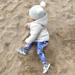 Girl on a beach wearing vibrant purple marbled Kids leggings.