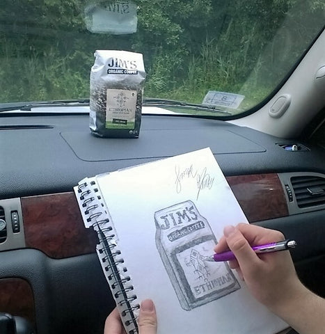 Artist sketching a bag of Jims Organic Coffee in the car