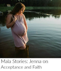 A pregnant woman with long auburn hair stands in a river with a wet pink sundress. She is wearing a sandalwood mala bead necklace from Mama Malas