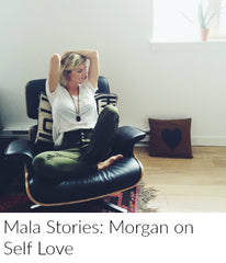 A blonde woman in a white tshirt and jeans relaxes with her arms above her head in a black lounge chair. She is wearing a sandalwood, black onyx and amazonite mala bead necklace from Mama Malas.