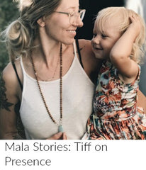 A young woman with tattoos and clear glasses holds her young blonde daughter in one arm, and holds the Amazonite guru stone of her sandalwood mala bead necklace in the other hand.