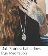 Close up of a womans chest. Her hair is long and she holds one tattooed arm over her heart. She is wearing a sandalwood, pearl and agate mala bead necklace by mama malas