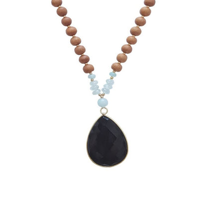 Close up image on a white background of a mala necklace with a pear shaped Black Onyx guru bead that is edged in gold. Above the guru bead are small Aquamarine and Amazonite beads followed by 6mm sandalwood beads separated by 2mm silver beads.
