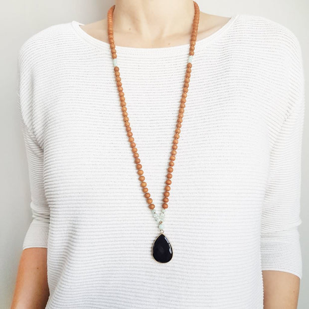 A woman stands in a white sweater wearing a sandalwood mala necklace. The mala has a  pear shaped Black Onyx guru bead that is edged in gold. Above the guru bead are small Aquamarine and Amazonite beads followed by 6mm sandalwood beads separated by 2mm silver beads.
