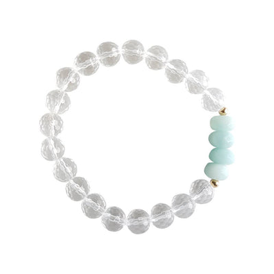 Close up image on a white background of a stretchy Amazonite and Clear Quartz mala bracelet. The bracelet has four faceted roundel beads made of Amazonite. The rest of the bracelet is made with 8mm faceted round Clear Quartz beads. Two small 2mm gold filled beads flank the Amazonite beads to separate them from the Clear Quartz.