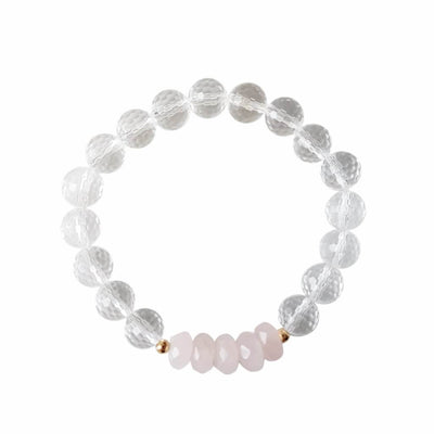Close up image on a white background of a stretchy Rose Quartz and Clear Quartz mala bracelet. The bracelet has four faceted roundel beads made of Rose Quartz. The rest of the bracelet is made with 8mm faceted round Clear Quartz beads. Two small 2mm gold filled beads flank the Rose Quartz beads to separate them from the Clear Quartz.