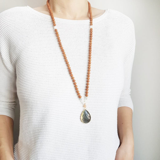A woman stands in a white sweater wearing a sandalwood mala necklace. The mala has a large 22x30mm teardrop shaped Labradorite guru bead with a border of gold.  The Labradorite has flashes of green and gold . Above the guru bead are Pink Moonstone, Rainbow Moonstone and Aquamarine beads followed by 6mm sandalwood beads separated by 2mm gold beads.
