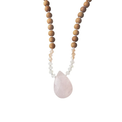 Close up image on a white background of a mala necklace with a faceted teardrop shaped Rose Quartz guru stone . Above the guru stone are small moonstone roundel beads and diamond shaped peach coloured beads followed by 6mm sandalwood beads separated by 2mm iridescent pink glass spacer beads.