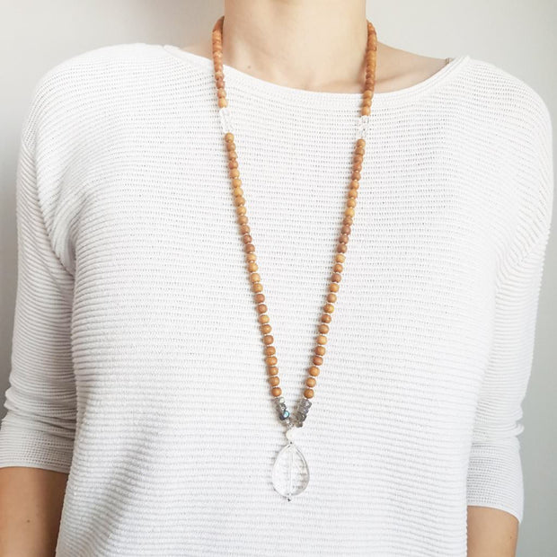 A woman stands in a white sweater wearing a sandalwood mala necklace. The mala has a faceted teardrop shaped Clear Quartz guru stone . Above the guru stone is a small mother of pearl bead and four roundel shaped labradorite beads going up on each side. The Labradorite has flashes of blue and green. The rest of the mala necklace is made with 6mm sandalwood beads separated by 2mm silver spacer beads.