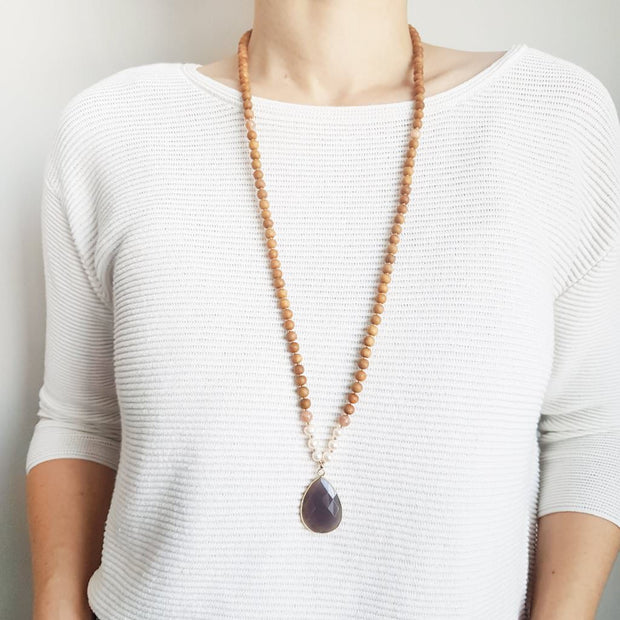 A woman stands in a white sweater wearing a sandalwood mala necklace. The mala has a faceted teardrop shaped Grey Moonstone guru stone edged with gold . On each side above the guru stone are three pearl beads and one pink moonstone bead. The rest of the mala necklace is made with 6mm sandalwood beads separated by 2mm gold spacer beads.