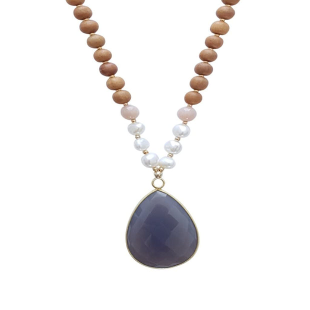 Close up image on a white background of a mala necklace with a 22x30mm faceted teardrop shaped Grey Moonstone guru stone edged with gold . On each side above the guru stone are three pearl beads and one pink moonstone bead. The rest of the mala necklace is made with 6mm sandalwood beads separated by 2mm gold spacer beads.