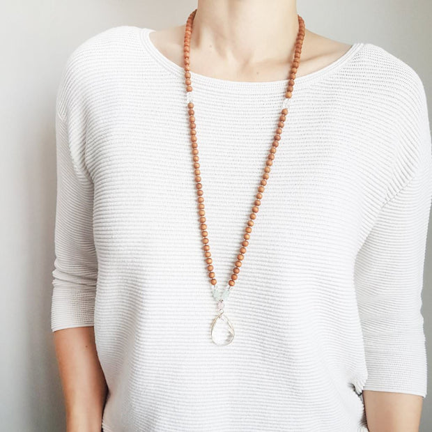 A woman stands in a white sweater wearing a sandalwood mala necklace. The mala has a 22x30mm faceted teardrop shaped Clear Quartz guru stone edged with gold . Above the guru stone is one 6mm Rose Quartz bead. On each side above the Rose Quartz are three small roundel aquamarine beads and one small faceted roundel Clear Quartz bead. The rest of the mala is made with 6mm sandalwood beads separated by 2mm gold spacer beads.