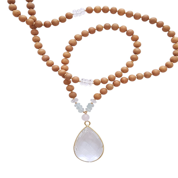 Close up image on a white background of a mala necklace. The mala has a 22x30mm faceted teardrop shaped Clear Quartz guru stone edged with gold . Above the guru stone is one 6mm Rose Quartz bead. On each side above the Rose Quartz are three small roundel aquamarine beads and one small faceted roundel Clear Quartz bead. The rest of the mala is made with 6mm sandalwood beads separated by 2mm gold spacer beads. Halfway up the necklace on each side is a small section of 3 roundel clear quartz beads.