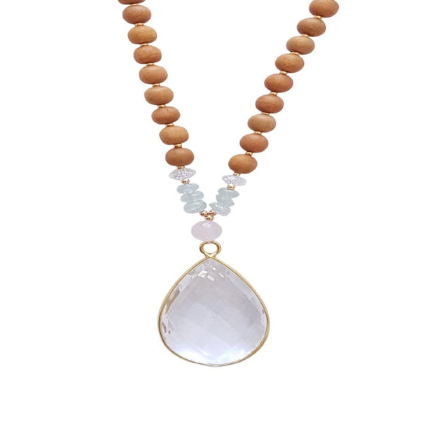 Close up image on a white background of a mala necklace. The mala has a 22x30mm faceted teardrop shaped Clear Quartz guru stone edged with gold . Above the guru stone is one 6mm Rose Quartz bead. On each side above the Rose Quartz are three small roundel aquamarine beads and one small faceted roundel Clear Quartz bead. The rest of the mala is made with 6mm sandalwood beads separated by 2mm gold spacer beads.