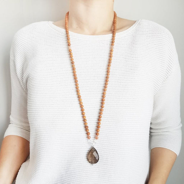 A woman stands in a white sweater wearing a sandalwood mala necklace. The mala has a faceted teardrop shaped Smoky Quartz Guru Bead . On each side above the Guru stone are two round faceted Clear Quartz beads and one round Pink Moonstone bead. The rest of the mala is made with 6mm sandalwood beads separated by 2mm silver spacer beads.