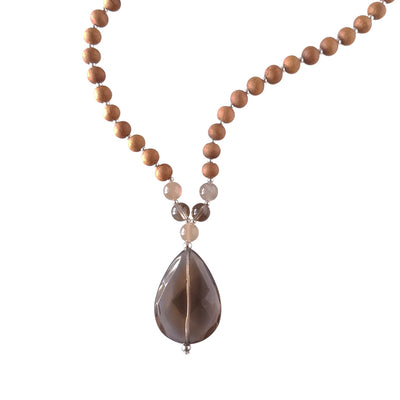 Close up image on a white background of a mala necklace. The mala has a  faceted teardrop shaped Smoky Quartz Guru Bead . Above the Guru stone is a single round grey moonstone bead. On each side, above the grey moonstone, is a 6mm round smoky quartz bead and another grey moonstone bead. The rest of the mala is made with 6mm sandalwood beads separated by 2mm silver spacer beads.