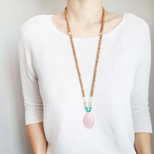 A woman stands in a white sweater wearing a sandalwood mala necklace. The mala has a large faceted teardrop shaped Rose Quartz Guru Bead . On each side above the guru stone, is two 6mm round turquoise beads, 2 serpentine beads and 2 green fluorite beads. The rest of the mala is made with 6mm sandalwood beads separated by 2mm silver spacer beads. In the middle of the necklace there is a single green fluorite bead on each side.