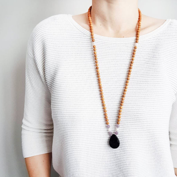 A woman stands in a white sweater wearing a sandalwood mala bead necklace. The mala has a  pear shaped faceted onyx guru bead.   On each side above the Onyx guru is one purple lepidolite bead, one pearl and one more lepidolite bead. The rest of the mala is made with 6mm sandalwood beads separated by 2mm silver spacer beads.