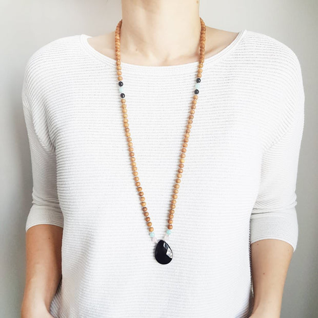 A woman stands in a white sweater wearing a sandalwood mala bead necklace. The mala has a  pear shaped faceted onyx guru bead.   On each side above the Onyx guru is one rose quartz bead and one light teal amazonite bead. The rest of the mala is made with 6mm sandalwood beads separated by 2mm silver spacer beads.  Two thirds of the way up the necklace a amazonite bead flanked by 2 onyx beads break up the sandalwood on each side.