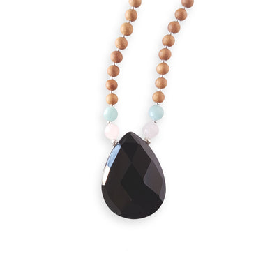Close up image on a white background of a mala bead necklace. The mala has a pear shaped faceted onyx guru bead.   On each side above the Onyx guru is one rose quartz bead and one light teal amazonite bead. The rest of the mala is made with 6mm sandalwood beads separated by 2mm silver spacer beads.