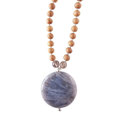 Close up image on a white background of a mala necklace with a round Flower Agate Crystal guru bead. Above the guru bead are two 6mm smoky quartz beads followed by 6mm sandalwood beads separated by 2mm silver beads.