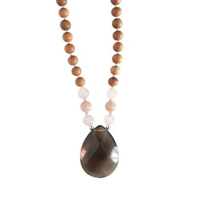 Close up image on a white background of a mala necklace with a teardrop shaped Smoky Quartz  guru bead. Above the guru bead are rose quartz and light pink moonstone beads followed by 6mm sandalwood beads separated by 2mm silver beads.