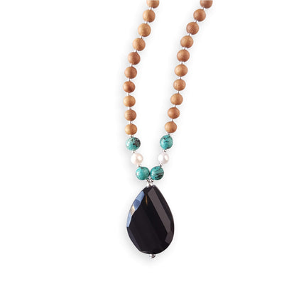 Close up image on a white background of a mala necklace with a teardrop shaped Black Onyx guru bead . Above the guru bead are pearl and turquoise jasper beads followed by 6mm sandalwood beads separated by 2mm silver beads.