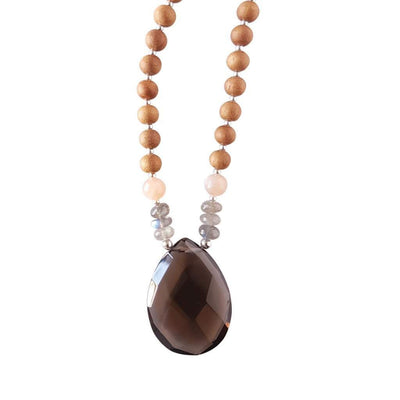 Close up image on a white background of a mala necklace with a pear shaped Smoky Quartz guru bead . Above the guru bead are pink moonstone and labradorite beads followed by 6mm sandalwood beads separated by 2mm silver beads.