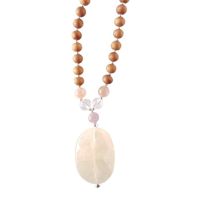 Close up image on a white background of a mala necklace with an oval shaped Yellow Calcite guru bead. Above the guru bead are Lepidolite, Clear Quartz and Pink Moonstone beads followed by 6mm sandalwood beads separated by 2mm silver beads.