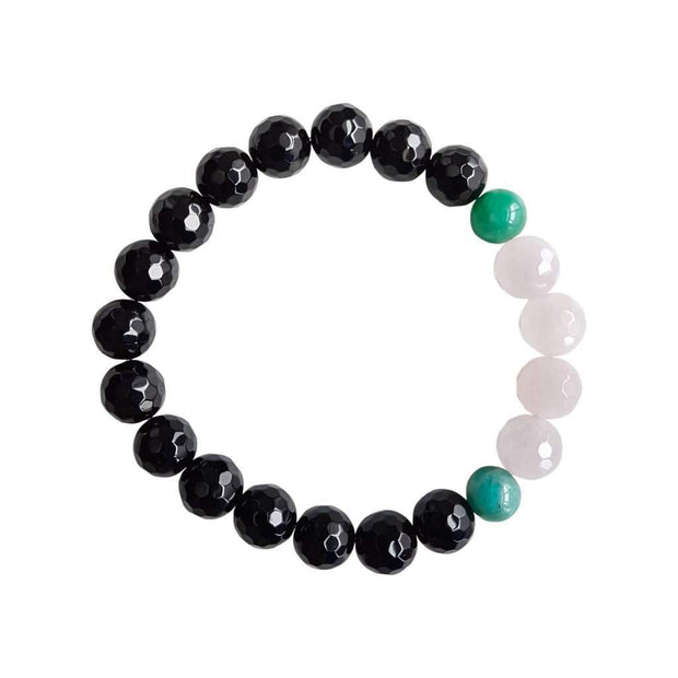 Close up on a white background of a faceted gemstone bracelet. There are four rose quartz beads in between two dark green amazonite beads. The rest of the bracelet is black onyx beads.