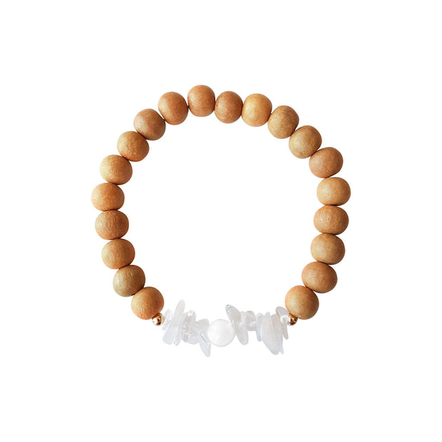 Close up image on a white background of a sandalwood mala bracelet. The bracelet has a 6mm round faceted mother of pearl bead flanked by half an inch of chipped moonstone on each side. The remainder of the bracelet is 8mm sandalwood beads.