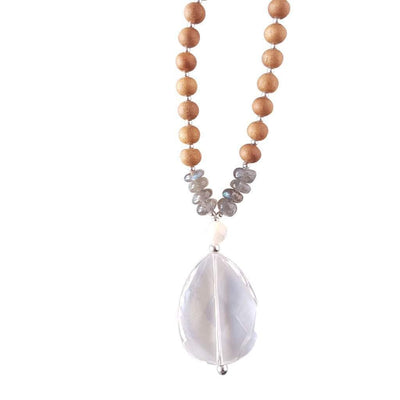 Close up image on a white background of a mala necklace with a faceted teardrop shaped Clear Quartz guru stone . Above the guru stone is a small mother of pearl bead and four roundel shaped labradorite beads going up on each side. The labradorite has flashes of brilliant light blue. The rest of the mala necklace is made with 6mm sandalwood beads separated by 2mm silver spacer beads.