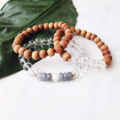 Three mala bracelets sit on a large leaf. One is made entirely with 8mm sandalwood beads. The second bracelet is made with 8mm sandalwood beads and has a section of four Clear Quartz beads. 2mm gold spacer beads separate the clear quartz from the sandalwood. The third bracelet has 8mm Clear Quartz Beads. It has an accent area with a 6mm faceted Mother of Pearl Bead in the middle of 6 faceted roundel Labradorite beads.Two 2mm gold spacer beads separate the Labradorite from the Clear Quartz.