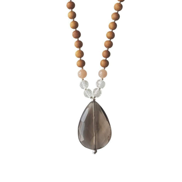 Close up image on a white background of a mala necklace. The mala has a  faceted teardrop shaped Smoky Quartz Guru Bead . On each side above the Guru stone are two round faceted Clear Quartz beads and one round Pink Moonstone bead. The rest of the mala is made with 6mm sandalwood beads separated by 2mm silver spacer beads.
