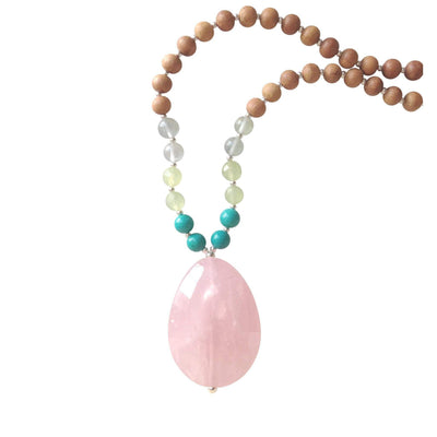 Close up image on a white background of a mala necklace. The mala has a  large faceted teardrop shaped Rose Quartz Guru Bead . On each side above the guru stone, is two 6mm round turquoise beads, 2 serpentine beads and 2 green fluorite beads. The rest of the mala is made with 6mm sandalwood beads separated by 2mm silver spacer beads.