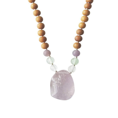 Close up image on a white background of a mala necklace. The mala has a slightly squared organic shaped light purple Amethyst Guru Bead . On each side above the guru stone, is one clear quartz, one green fluorite and one purple lepidolite bead. The rest of the mala is made with 6mm sandalwood beads separated by 2mm silver spacer beads.