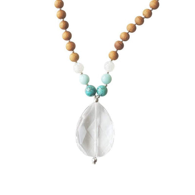 Close up image on a white background of a mala necklace. The mala has a faceted pear shaped Clear Quartz Guru Bead . On each side above the guru stone, is one turquoise, one light teal amazonite and one rainbow moonstone bead. The rest of the mala is made with 6mm sandalwood beads separated by 2mm silver spacer beads.