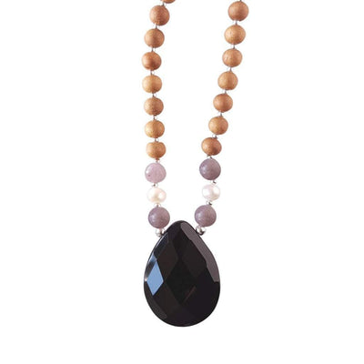 Close up image on a white background of a mala bead necklace. The mala has a pear shaped faceted onyx guru bead.   On each side above the Onyx guru is one purple lepidolite bead, one pearl and one more lepidolite bead. The rest of the mala is made with 6mm sandalwood beads separated by 2mm silver spacer beads.