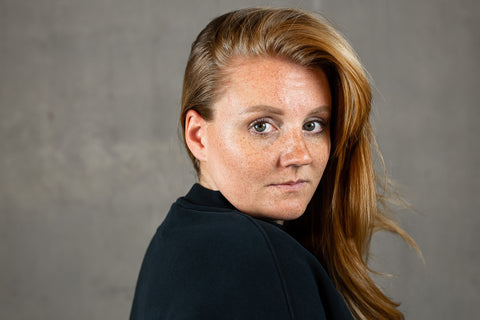 KIRA FOUNDER OF KIANI - PHOTO OF A WOMAN WITH GINGER HAIR LOOKS DIRECLY INTO THE CAMERA SHE IS WEARING THE SWEATSHIRT