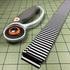 rotary cutter and strips of black and white fabric on cutting mat