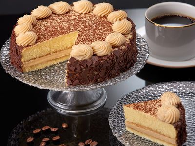 Two layers of coffee washed cake are filled with the traditional custard and topped with a light and delectable coffee whipped cream. As an extra touch, this delight is then sprinkled with dark chocolate and cocoa and adorned with a chocolate occasion plaque.