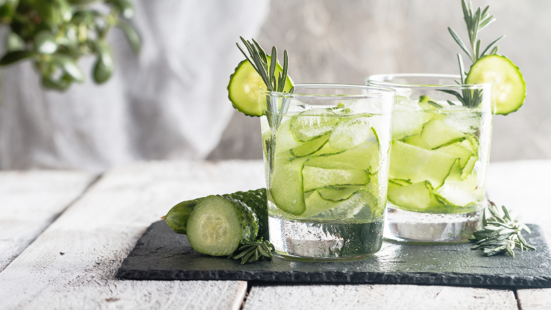 two glasses of water with cucumber slices in them sitting on tray on top of table